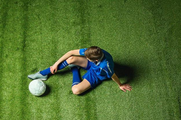 Calciatore del ragazzo che si siede sull'erba verde Foto Gratuite