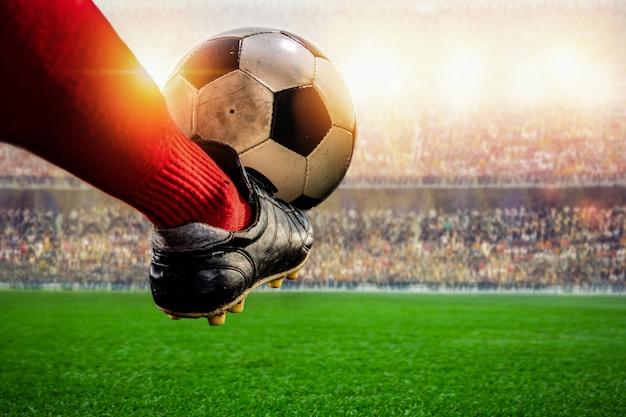 Calciatore rosso che calcia azione della palla nello stadio Foto Premium