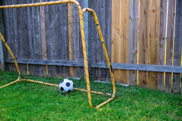 Calcio di chldren del cortile al recinto di legno con la parete Foto Premium