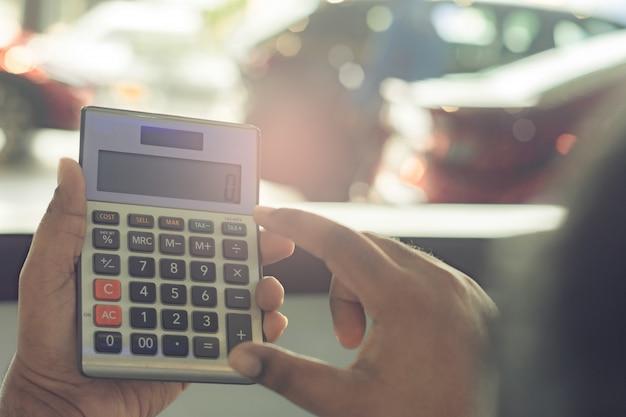 Calcolatore asiatico della tenuta dell'uomo per finanza di affari sul fondo del bokeh vago sala d'esposizione dell'automobile per l'automobile automobilistica o il trasporto del trasporto Foto Premium