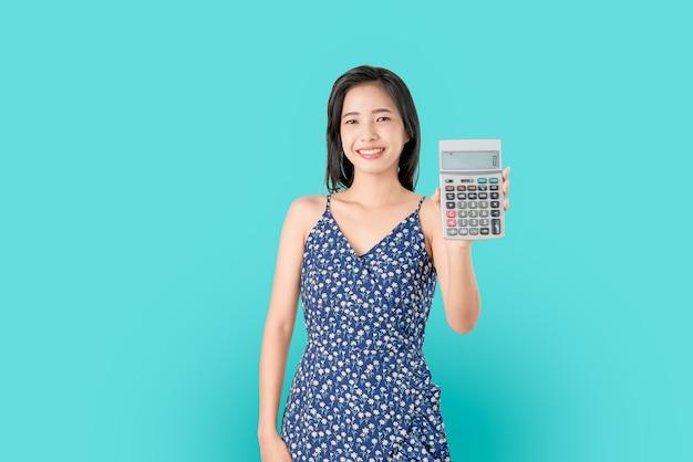 Calcolatore asiatico della tenuta della donna di sorriso isolato su fondo blu. Foto Premium