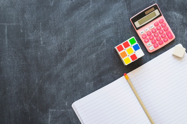 Calcolatore del taccuino e cubo di rubik sulla lavagna Foto Gratuite