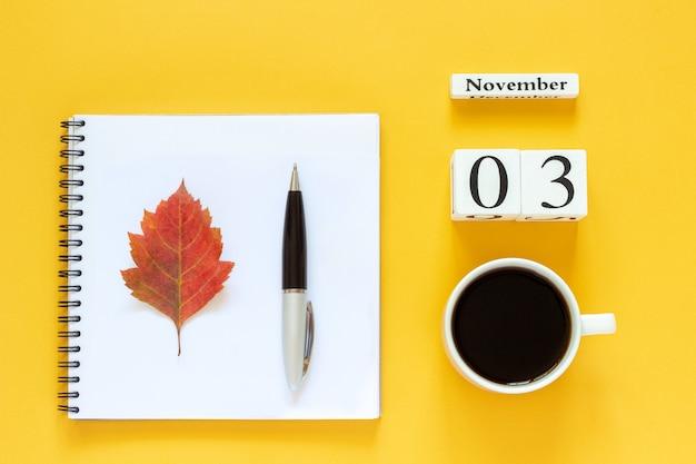 Calendario 03 novembre tazza di caffè, blocco note con penna e foglia gialla Foto Premium