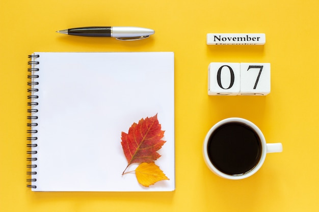 Calendario 07 novembre tazza di caffè, blocco note con penna e foglia gialla su sfondo giallo Foto Premium