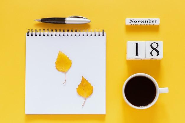 Calendario 18 novembre tazza di caffè, blocco note con penna e foglia gialla su sfondo giallo Foto Premium