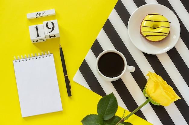Calendario 19 aprile. tazza di caffè, ciambella e rosa, blocco note su sfondo giallo. luogo di lavoro elegante Foto Premium