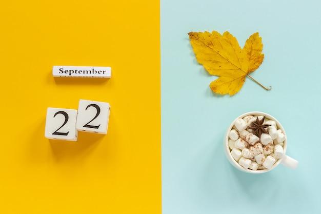 Calendario 22 settembre, tazza di cacao con marshmallow e foglie di autunno gialle su sfondo blu giallo. Foto Premium