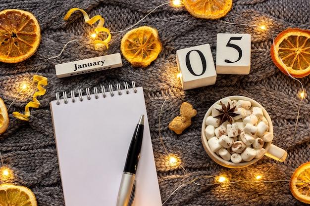 Calendario 5 gennaio coppa di cacao e blocco note aperto vuoto Foto Premium