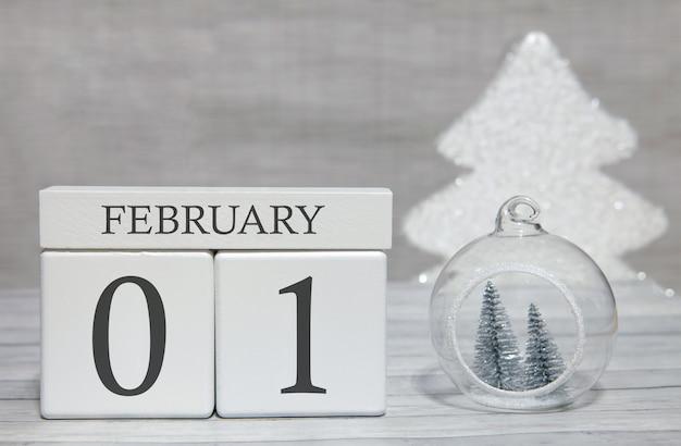 Calendario a forma di cubo per il 1 febbraio su superficie di legno e sfondo chiaro Foto Premium
