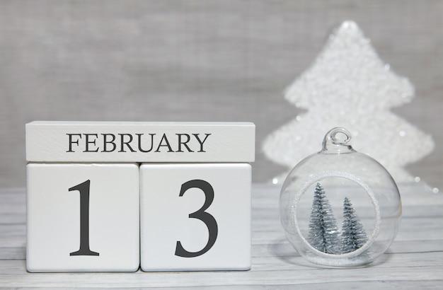 Calendario a forma di cubo per il 13 febbraio su superficie di legno e sfondo chiaro Foto Premium