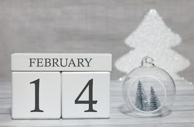 Calendario a forma di cubo per il 14 febbraio su superficie di legno e sfondo chiaro Foto Premium