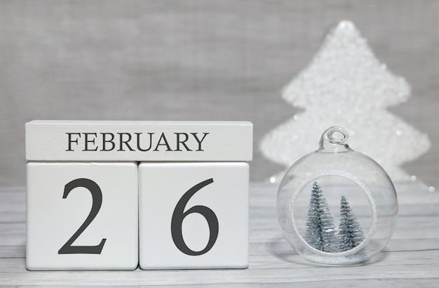 Calendario a forma di cubo per il 26 febbraio su superficie di legno e sfondo chiaro Foto Premium