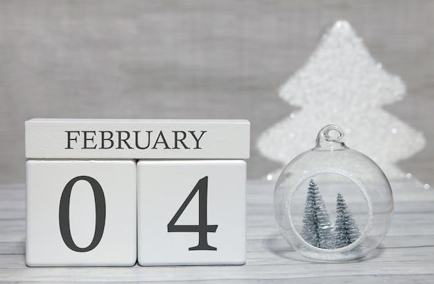 Calendario a forma di cubo per il 4 febbraio su superficie di legno e sfondo chiaro Foto Premium