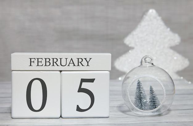 Calendario a forma di cubo per il 5 febbraio su superficie di legno e sfondo chiaro Foto Premium