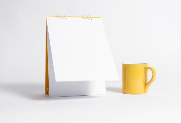 Calendario a spirale di carta bianca e tazza gialla per modello di modello Foto Premium