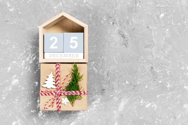 Calendario con data 25 dicembre e scatole regalo su colore Foto Premium