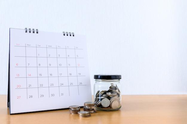 Calendario con giorni e moneta nel barattolo sul tavolo di legno Foto Premium