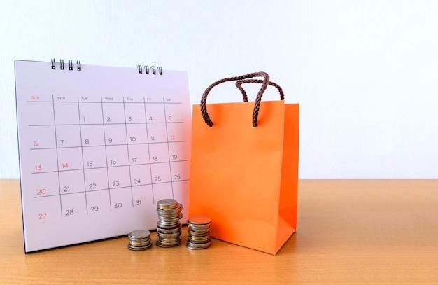 Calendario con giorni e sacco di carta arancione sul tavolo di legno. concetto di acquisto Foto Premium