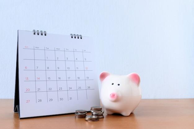 Calendario con giorni e salvadanaio sul tavolo di legno Foto Premium