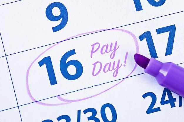 Calendario con il cerchio dell'indicatore nella parola giorno di paga Foto Premium