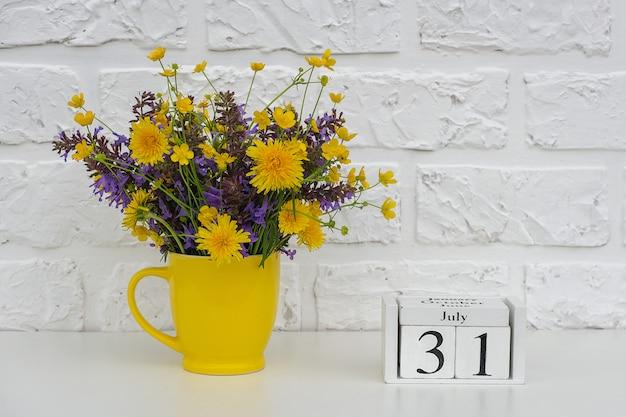 Calendario cubi 31 luglio e tazza gialla con fiori colorati luminosi contro il muro di mattoni bianchi Foto Premium