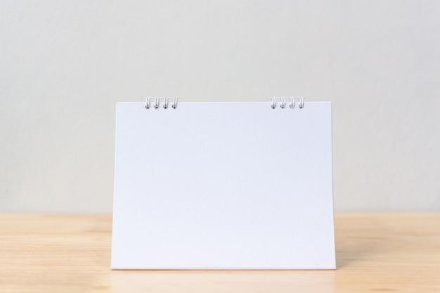Calendario da tavolo bianco sul tavolo di legno. Foto Premium