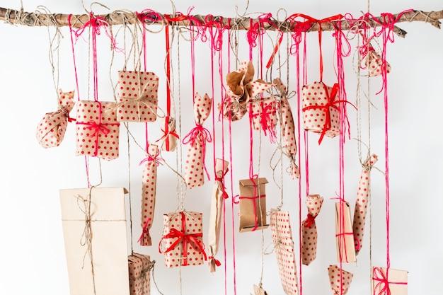 Calendario di avvento fatto a mano appeso a un muro bianco. regali avvolti in carta artigianale e legati con fili e nastri rossi. bastone di legno e tanti regali Foto Premium
