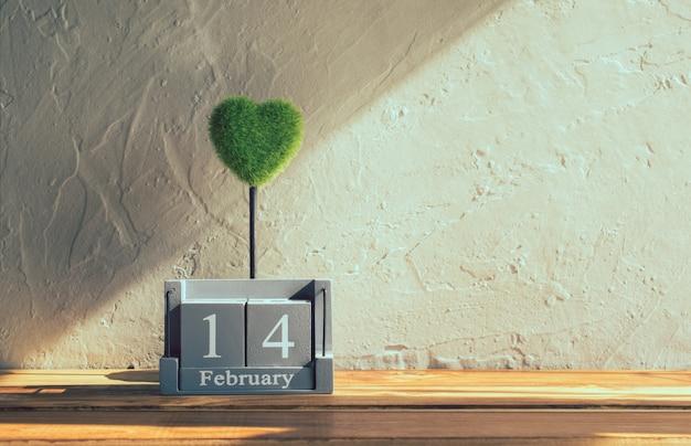 Calendario di legno d'annata per il 14 febbraio con cuore verde sulla tavola di legno Foto Premium