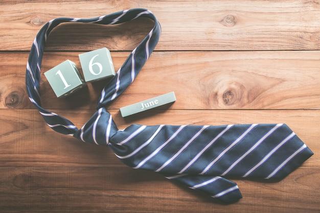 Calendario di legno d'annata per il 16 giugno con il concetto del fondo dell'iscrizione di festa del papà felice della cravatta. Foto Premium