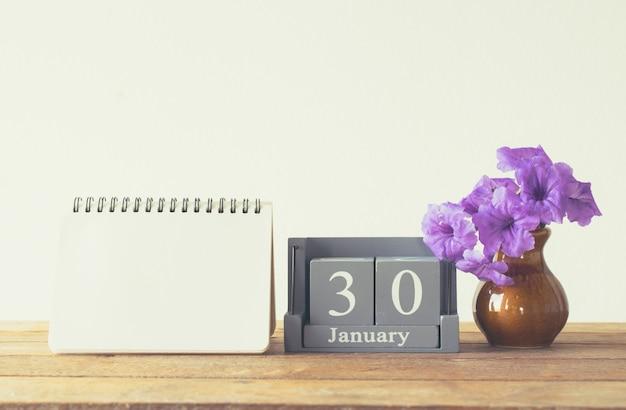 Calendario di legno d'annata per il giorno 30 gennaio sulla tavola di legno con lo spazio vuoto del taccuino per testo. Foto Premium