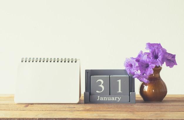 Calendario di legno d'annata per il giorno 31 gennaio sulla tavola di legno con il taccuino vuoto Foto Premium