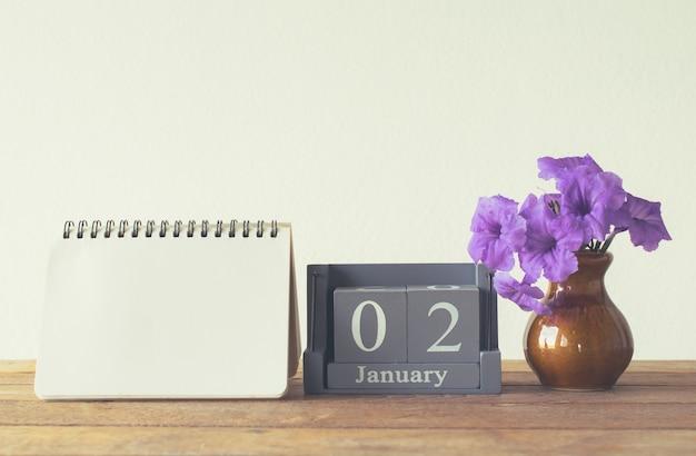 Calendario di legno dell'annata per il giorno di gennaio 2 sulla tavola di legno con lo spazio vuoto del taccuino per testo. Foto Premium
