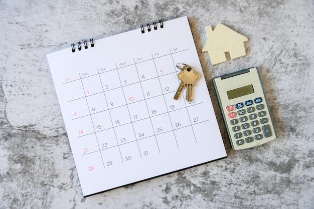 Calendario e casa sul tavolo. giorno di acquisto o vendita di una casa o pagamento per affitto o prestito. Foto Premium