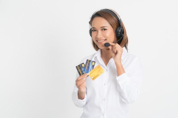 Call center della donna con la tenuta della cuffia avricolare e la carta di credito. Foto Premium