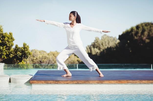 Calma bruna facendo yoga in piscina Foto Premium