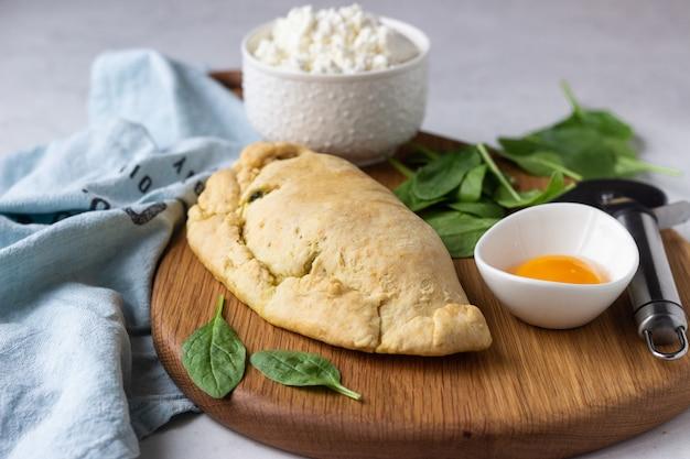 Calzone chiuso per pizza con spinaci, pollo e ricotta. cibo italiano. Foto Premium