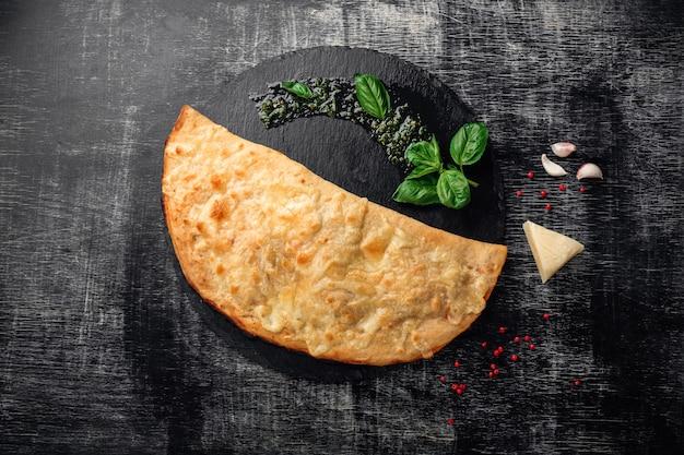 Calzone tradizionale pizza italiana con ingredienti su una pietra e fondo in legno scuro graffiato Foto Premium