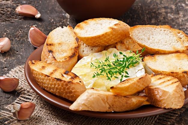Camembert al forno con timo e toast strofinati con aglio Foto Premium