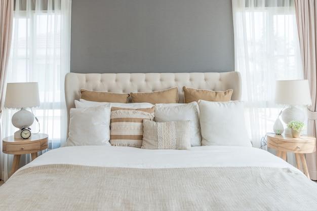 Camera da letto in tenui colori chiari. grande letto matrimoniale comodo in elegante camera da letto classica a casa. Foto Premium
