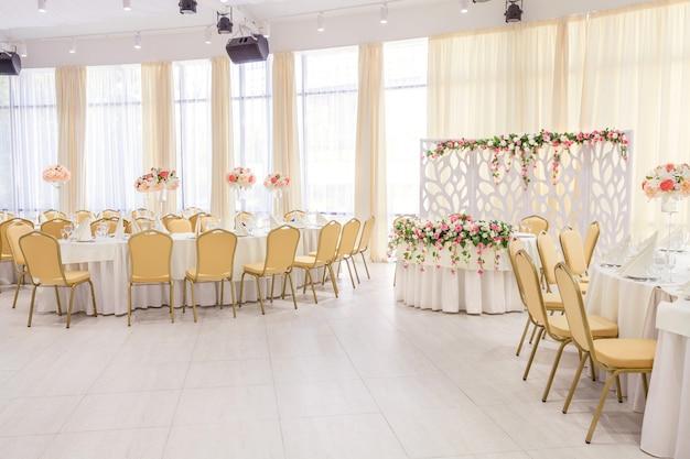 Camera splendidamente decorata con tavoli coperti con fiori nel ristorante Foto Premium