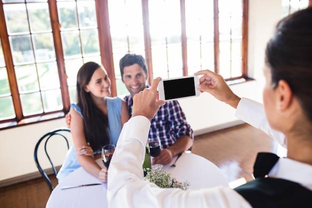 Cameriera di bar che fa clic sulla foto di una coppia in ristorante Foto Premium