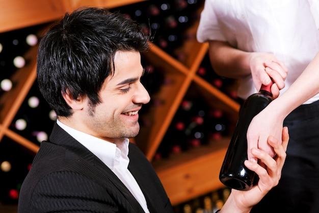 Cameriera nel ristorante che offre vino rosso Foto Premium