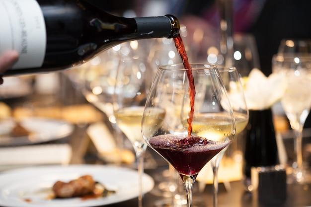 Cameriera versare vino rosso nel bicchiere sul tavolo in ristorante Foto Premium