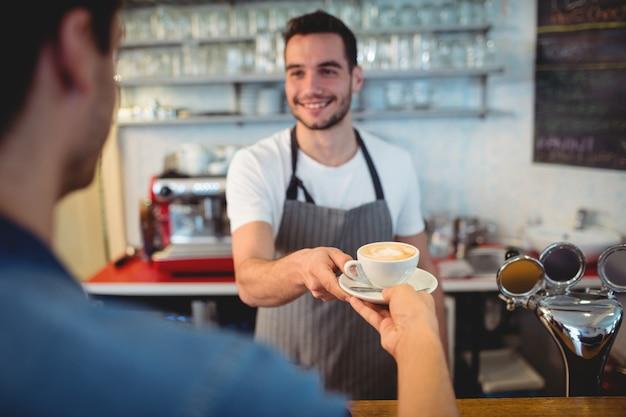 Cameriere bello che serve caffè al cliente maschio al self-service Foto Premium