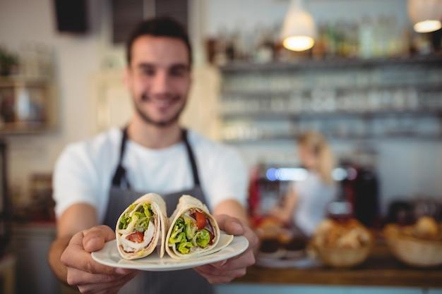 Cameriere che offre panini freschi al caffè Foto Premium