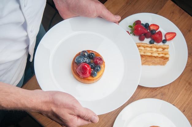 Cameriere che porta il dessert alla frutta Foto Gratuite