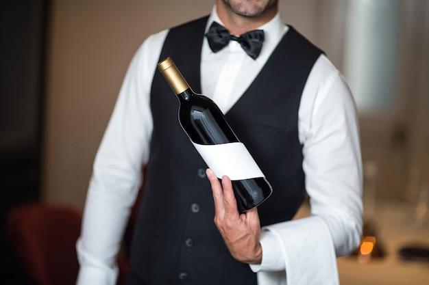 Cameriere che presenta vino rosso Foto Premium