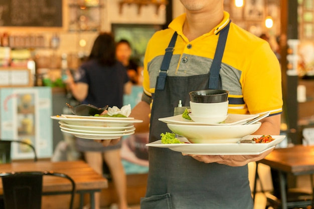 Cameriere che rimuove i piatti sporchi dai tavoli nel ristorante. Foto Premium