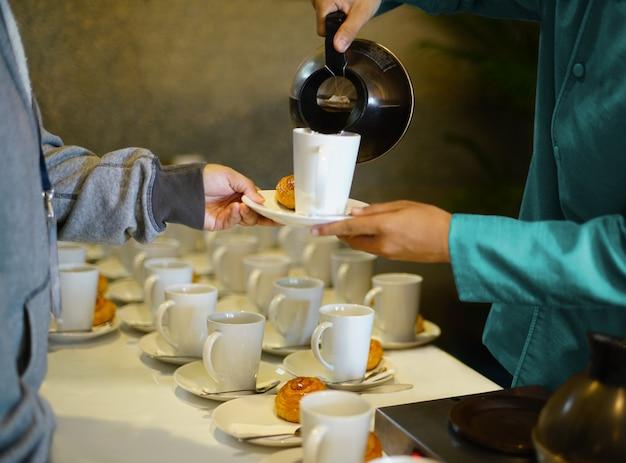 Cameriere che versa il caffè o il tè caldo nella tazza bianca e serve il piatto da forno per la pausa caffè alla festa Foto Premium