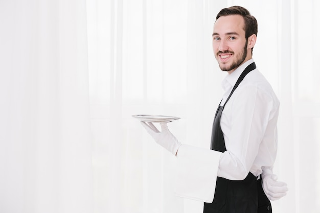 Cameriere di smiley con piastra guardando la fotocamera Foto Gratuite